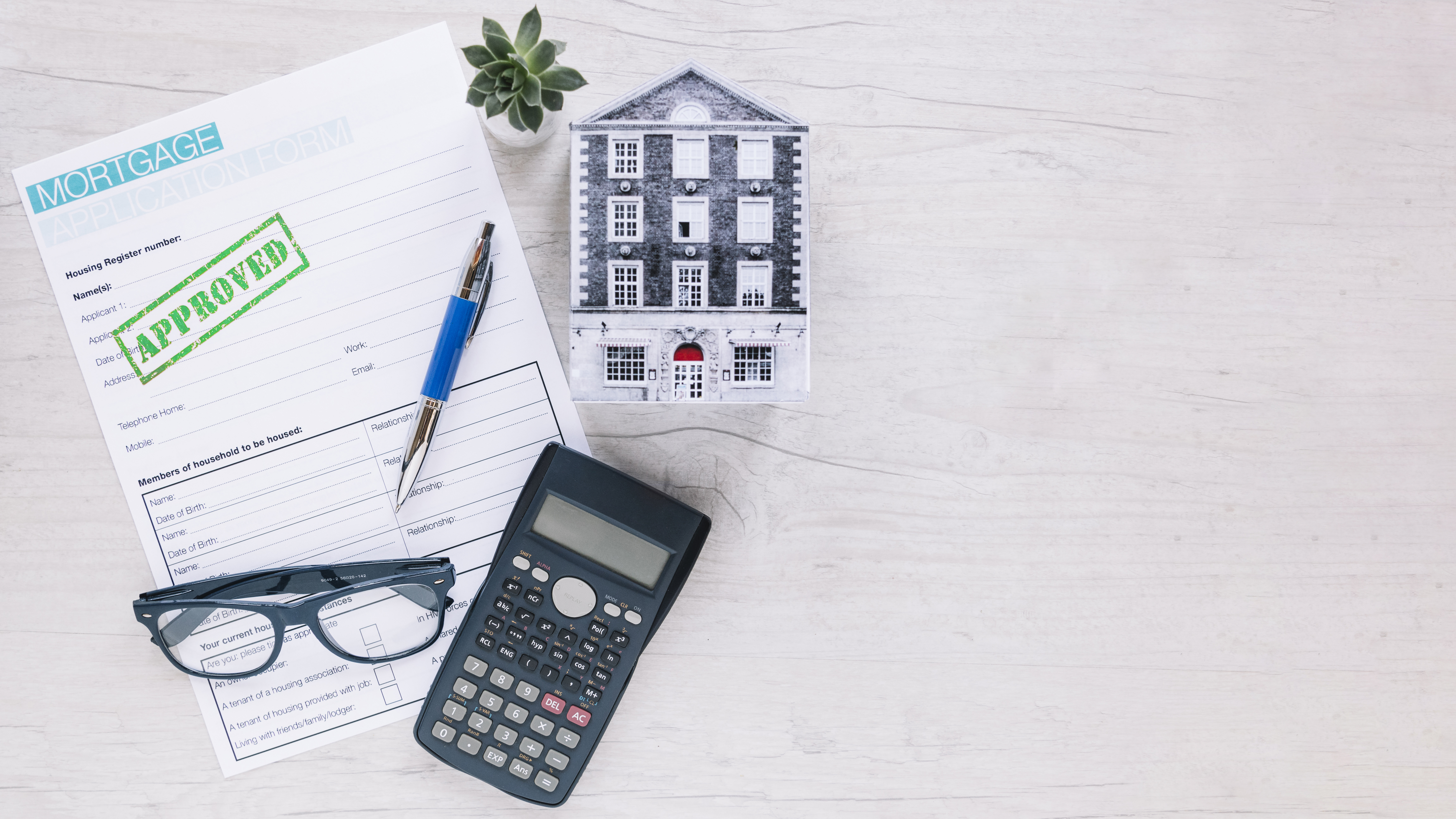 calculator, mortgage approval form, eyeglass and cutout housing sitting on a white background