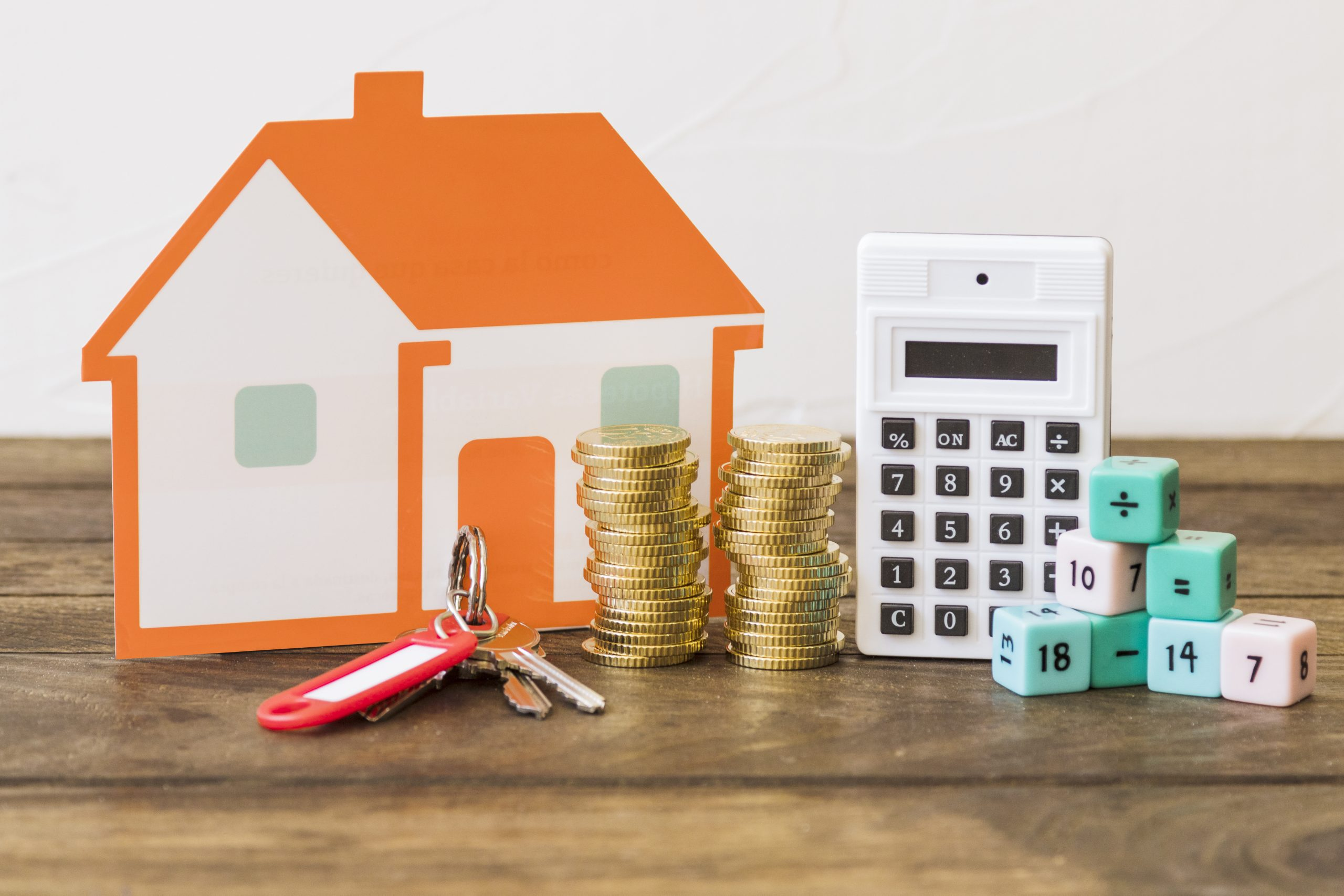 Paper house with a key, stack of coins and calculator